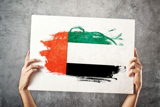 United Arab Emirates flag. Man holding banner with UAE Flag.