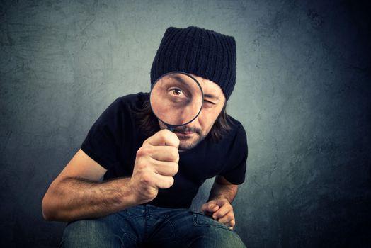 Man looking through magnifying glass