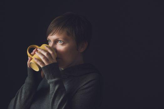 Beautiful Woman Drinking Coffee in Dark Room