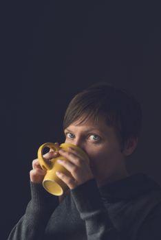 Beautiful Woman Drinking Coffee or Tea in Dark Room