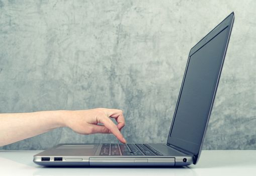 Woman pressing keypad on laptop computer