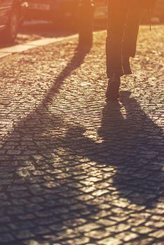 Running Boy Shadow on Cobblestone Pavement