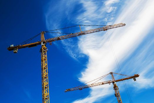 Industrial Cranes Working on Construction Site Against Blue Sky