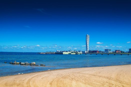 MALMO, SWEDEN - JUNE 26, 2015: Sandy Beach and Malmo West Harbor Area Cityscape with Turning Torso as Distinctive Landmark of this Swedish Town and Largest Building in Scandinavia.