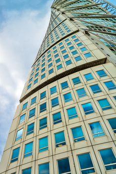MALMO, SWEDEN - JUNE 25, 2015: Malmo Turning Torso, Distinctive Swedish City Landmark is designed by Spanish architect Santiago Calatrava and belongs to Neo-futuristic architectural style.