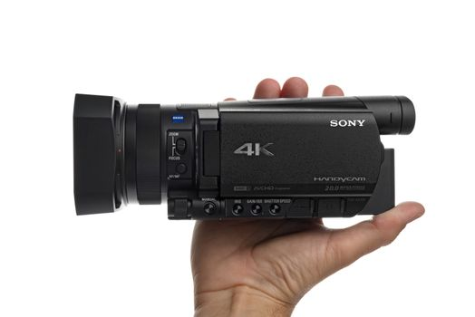 NOVI SAD, SERBIA - APRIL 25, 2015: Person holding Sony FDR AX100, 4k UHD Handycam Camcorder captures Ultra High Definition Footage. Illustrative editorial for product isolated on white background.