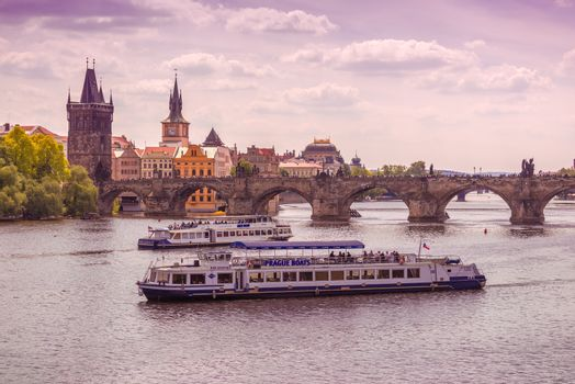 PRAGUE, CZECH REPUBLIC - MAY 22, 2015: Prague Charles Bridge and Tourist Looking at UNESCO Heritage from Boats Floating on River Vltava.