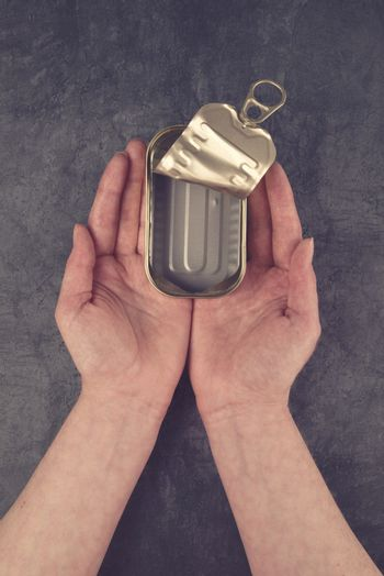 Female Hands Holding Open Empty Sardine Fish Tin Can