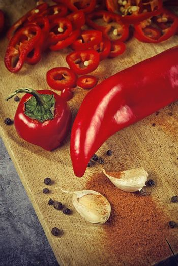 Red Hot Chili Pepper, Spice and Organic Garlic on Wooden Kitchen Plate as Hot Food Ingredients for Spicy Piquant Cuisine. Selective focus with shallow depthof field.