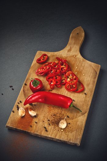 Red Hot Chili Pepper, Spice and Organic Garlic on Wooden Kitchen Plate as Hot Food Ingredients for Spicy Piquant Cuisine.