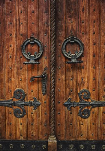 Old carved wooden door with hinges