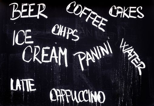 Restaurant Advertising Blackboard with Beverage, Food and Drink Refreshment Drinks List Written in Chalk: Beer, Coffee, Cakes, Ice Cream, Chips, Panini, Water, Latte, Cappuccino.