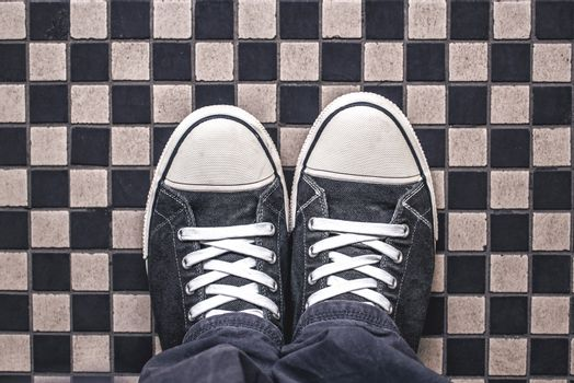 Gray Sneakers on Checkered Pattern Pavement, Top View