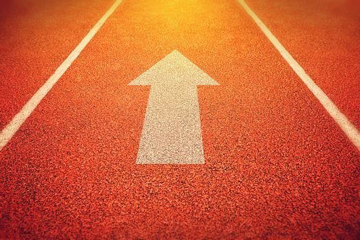 Athlete Running Track with an Arrow Pointing Forward as Motivation and Inspiration Symbol for designs or graphic posters background, Instagram Like Toned Image with Selective Focus.