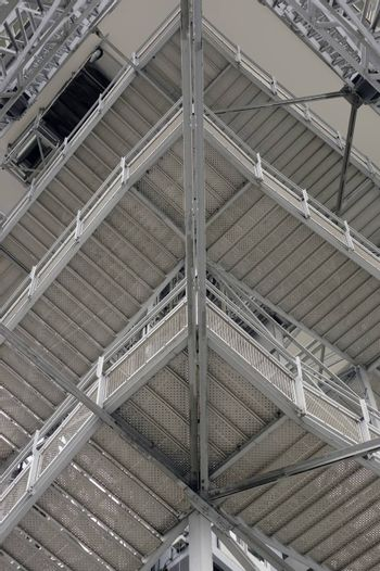 The low angle view of a square steel staircase rising over several floors.