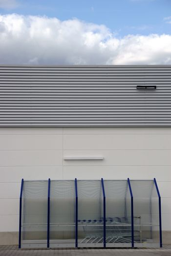 A plastic shelter with shopping baskets on the wall of a shopping mall.