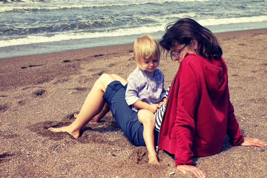 Mother and her little daughter sitting on the beach with serious facial expressions