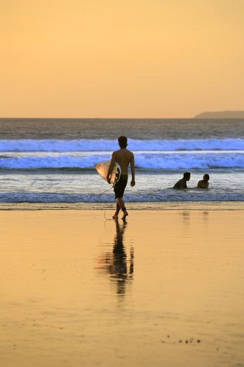 Bali, Indonesia - October 30, 2008: Silhouette of surfer with a board on a sunset. Bali, Indonesia