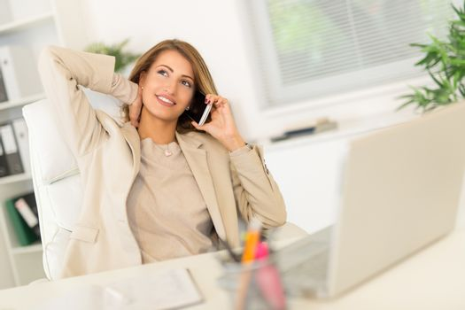 Businesswoman Phoning In Office
