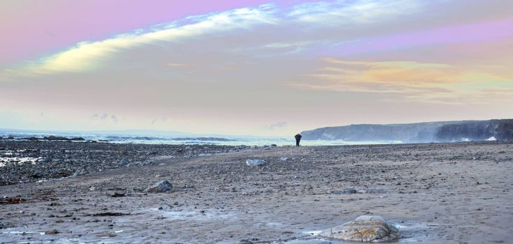 man walking at rocky beach near ballybunion on the wild atlantic way ireland with a beautiful yellow sunset