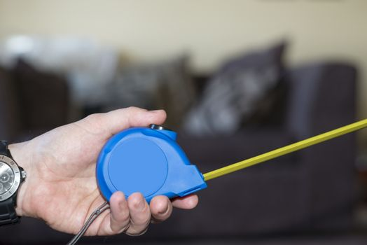 measuring tape in hand for do it yourself home improvements