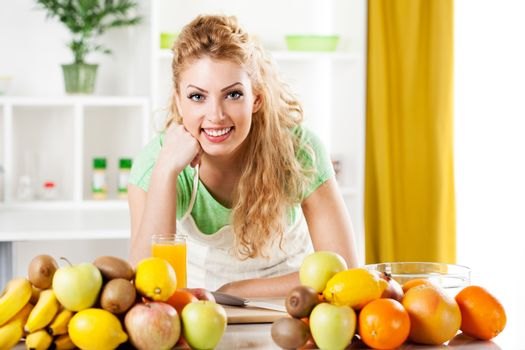 Beautiful young woman in a kitchen with fruits. Looking at camera.