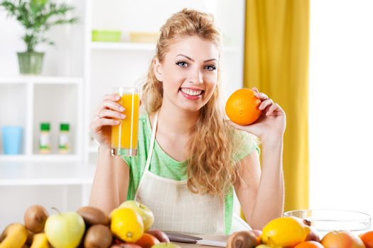 Beautiful young woman in a kitchen, holding an orange and juice. Looking at camera.