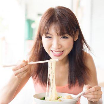 Asian girl eating ramen