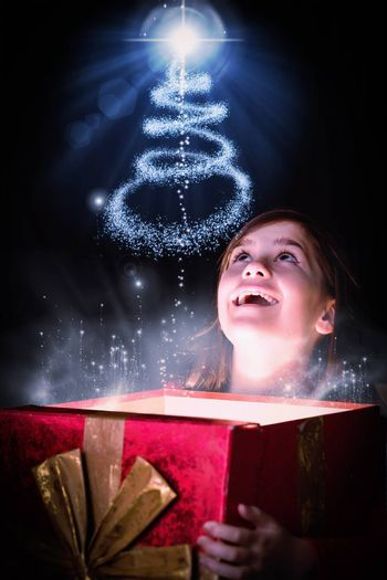 Little girl opening a magical christmas gift against christmas tree design