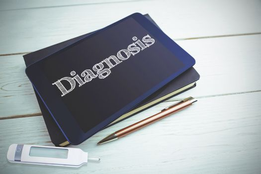 Diagnosis against view of a book and tablet lying on desk