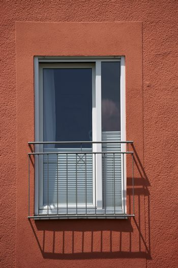 A railing in front of a window of a residential building casts a shadow.