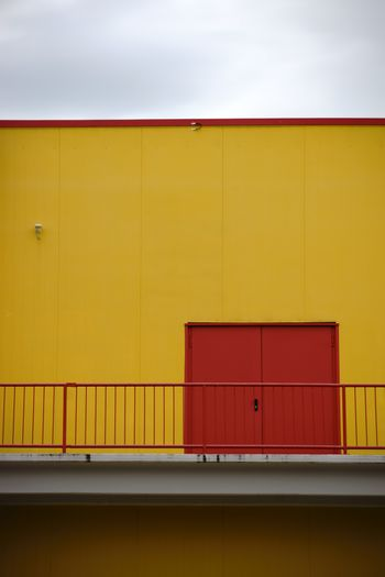 A colorful and striking sidewall of a shopping center with an emergency exit and a railing on the first floor.