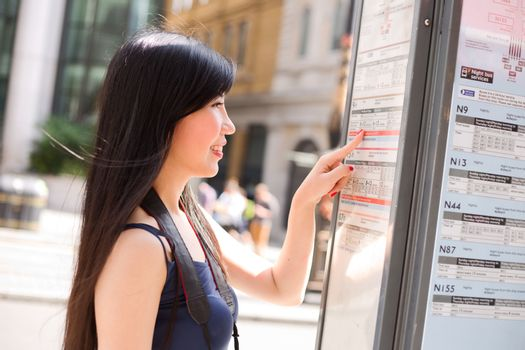 japanese lady at the bus stop checking the schedule