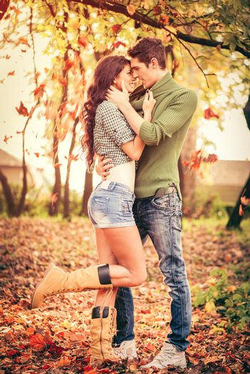 Young heterosexual couple in love in park, standing on fallen leaves, leaning their heads at each other, looking at each other and smiling.