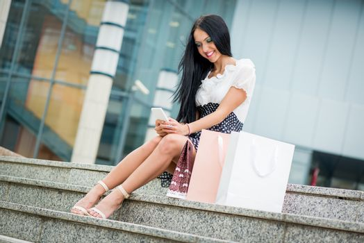 Cheerful girl after shopping with many shopping bags sitting on stairs in the shopping mall and  looking at smart phone.