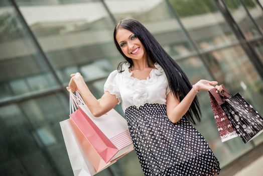 Happy girl in shopping passes in front of window shopping mall carrying bags in their hands.