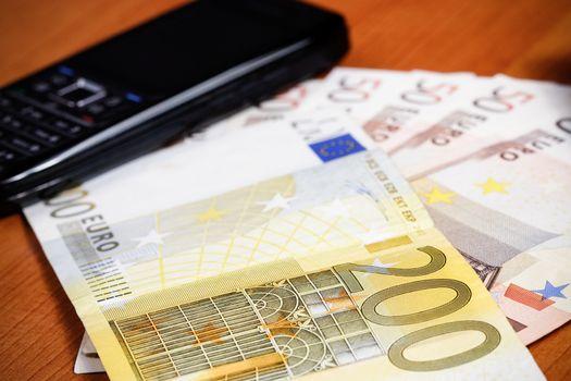 Mobile phone on many euro background