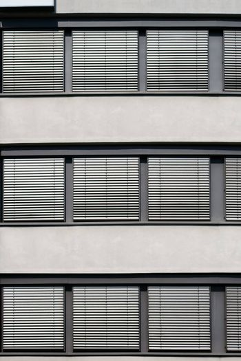 The modern facade of an office building with a row of windows and metal shutters.