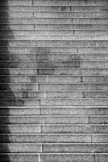The close-up of steep stairs where a lantern casts a shadow.