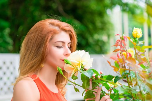 young woman enjoying the scent of blooming roses