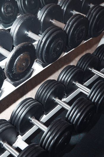 Group of barbells arranged in row at the gym. Vertical photo