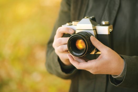 Hipster female photographer shooting outdoors