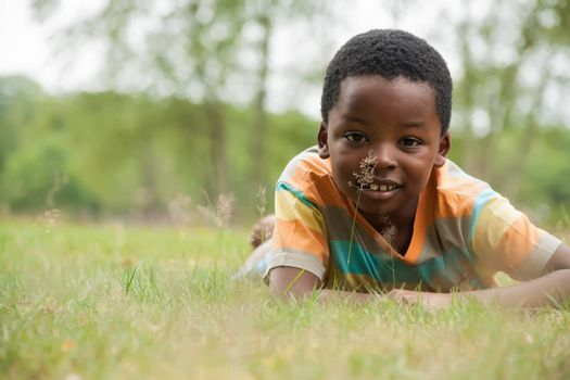 African boy is relacing in the grass