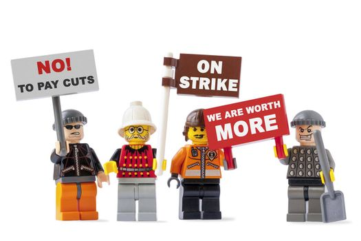 VILNIUS, LITHUANIA - MAY 12, 2015:Workers on strike concept with four Lego toy figurines isolated on white background and holding signs with protest messages