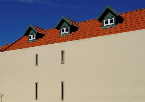 A house with red tile roof and three garrets