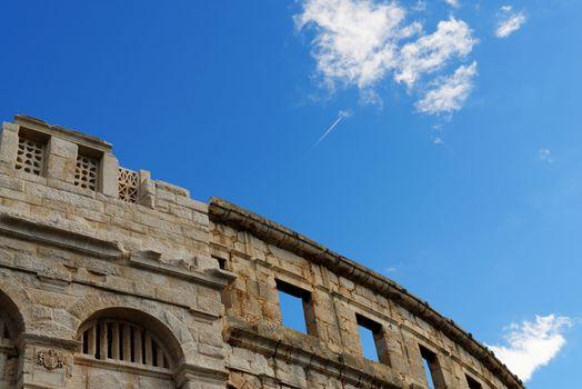 Contrail of the jet plane above ancient Roman amphitheater in Pula, Croatia