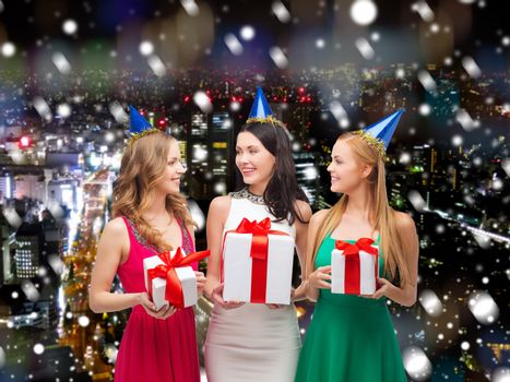 presents, holidays, people and celebration concept - smiling women in party caps with gift boxes over snowy night city background