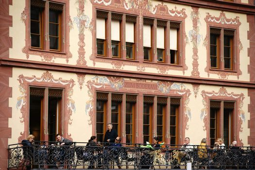 """Mainz, Germany - September 25, 2015: The magnificently painted facade of the house """"to Boderam"""" on the market in Mainz with a cafe terrace and visitors on September 25, 2015 in Mainz."""