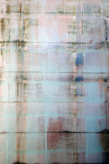The abstract slurred metal surface of a water tank with rust and traces of water.