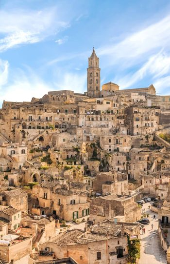 panoramic view of typical stones (Sassi di Matera) and church of Matera UNESCO European Capital of Culture 2019 under blue sky